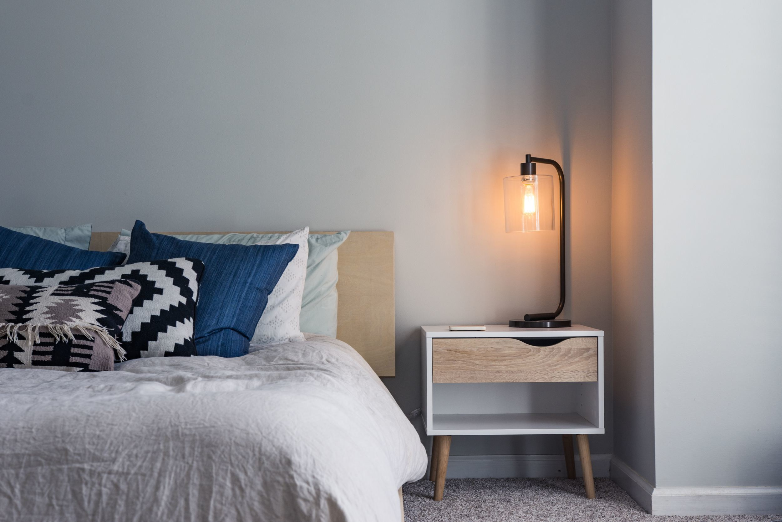 a made bed with a nightstand and an industrial lamp thats turned on