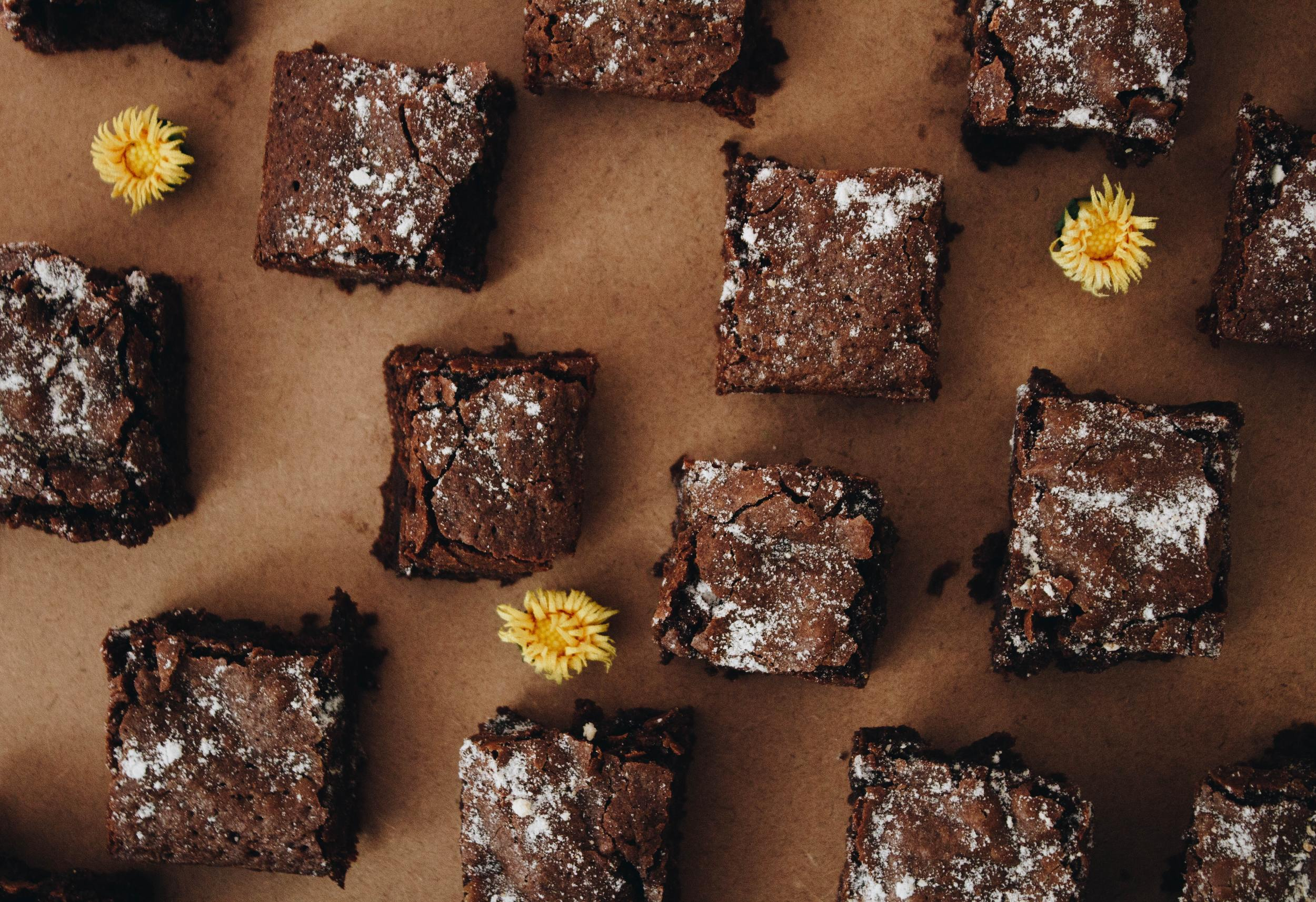 Moist and gooey chocolate brownie bites, on a cutting board with decorative, edible flowers around them