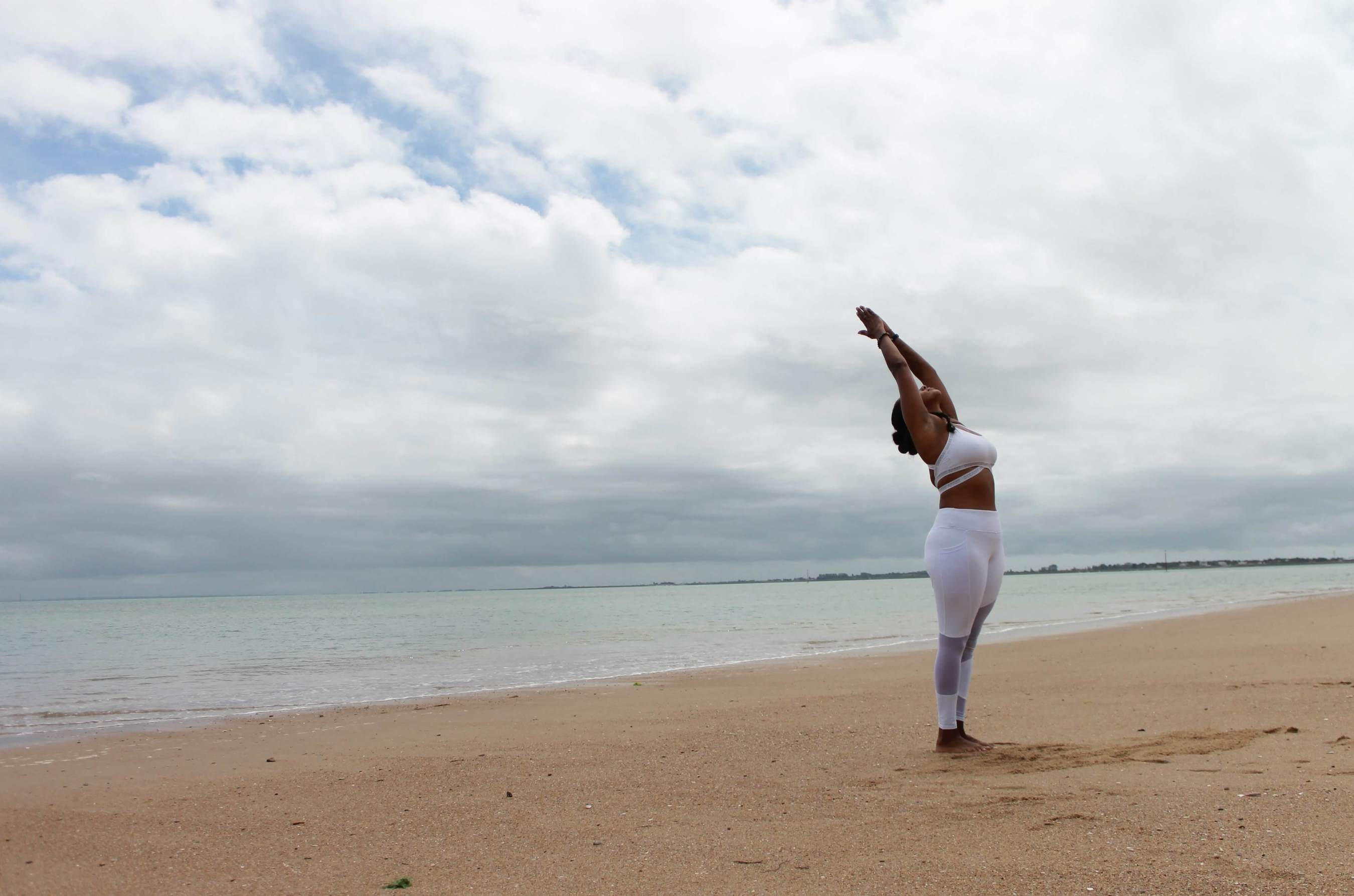 A woman is standing on an empty, peaceful beach. She's wearing white exercise clothes and stretching, greeting the day.