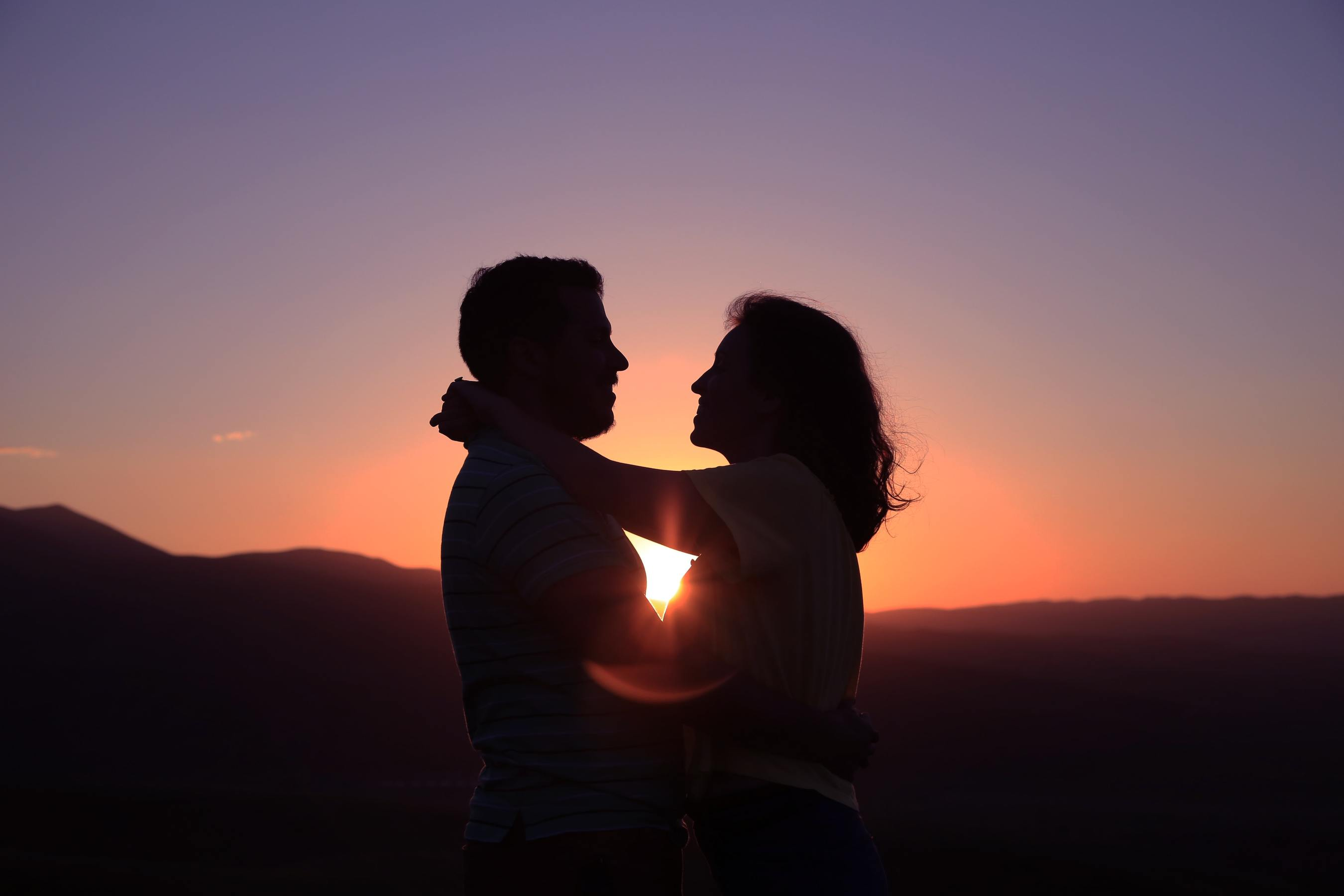 A couple embracing against a sunset