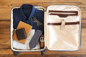 an open packed suitcase with a man's suit