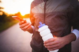 a closeup of someone holding a water bottle and a cell phone