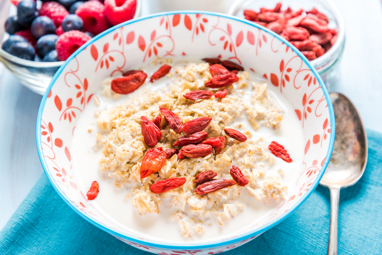 a bowl of oats and milk with gogi berries on top