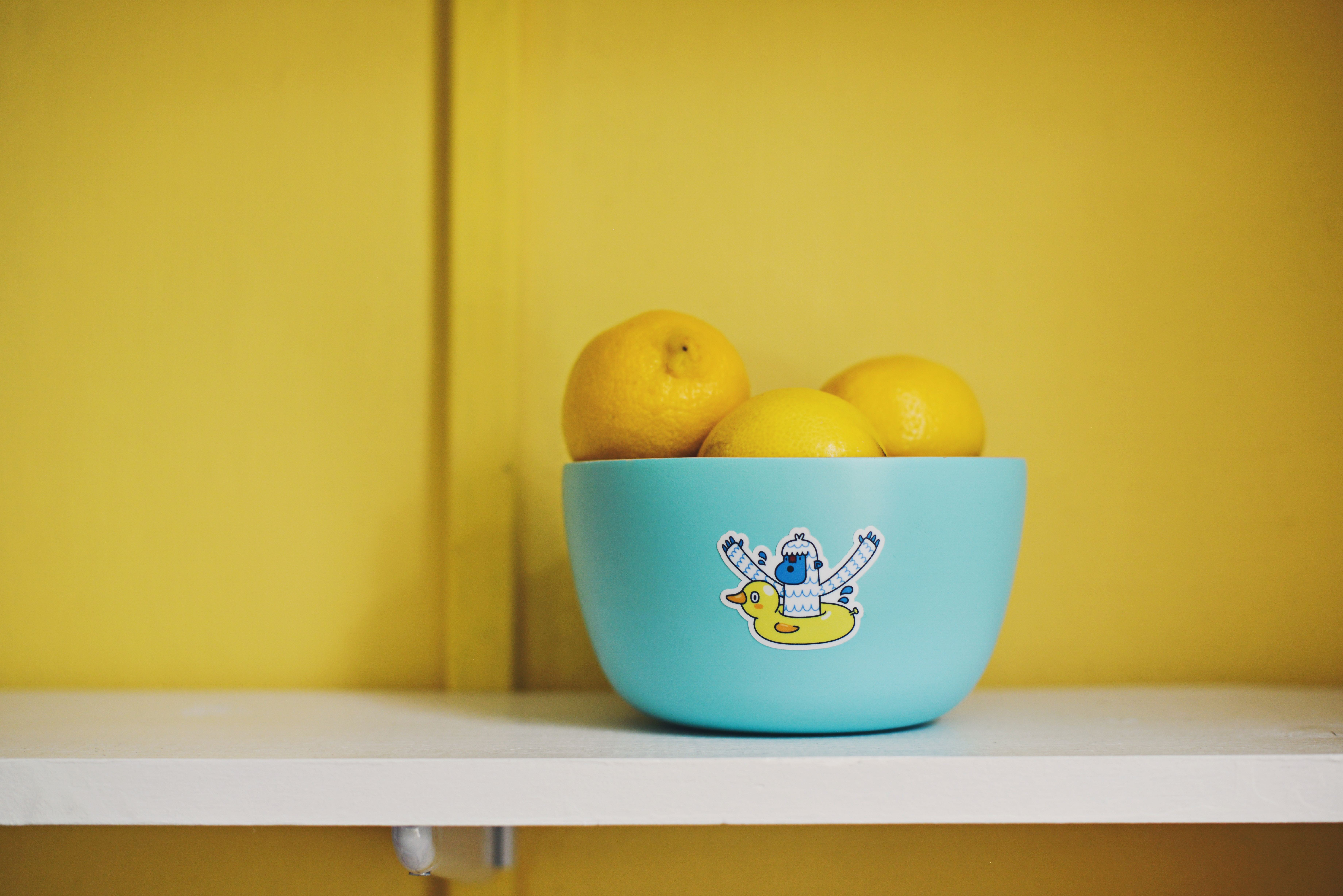 lemons in a blue bowl against a yellow wall
