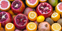 photo of cut open pomegranates, oranges, and lemons