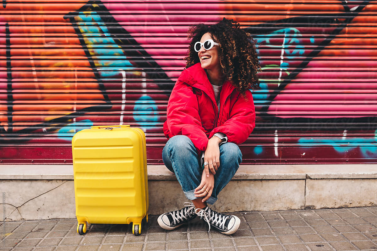 a black woman smiling sitting on a curb with her yellow suitcase