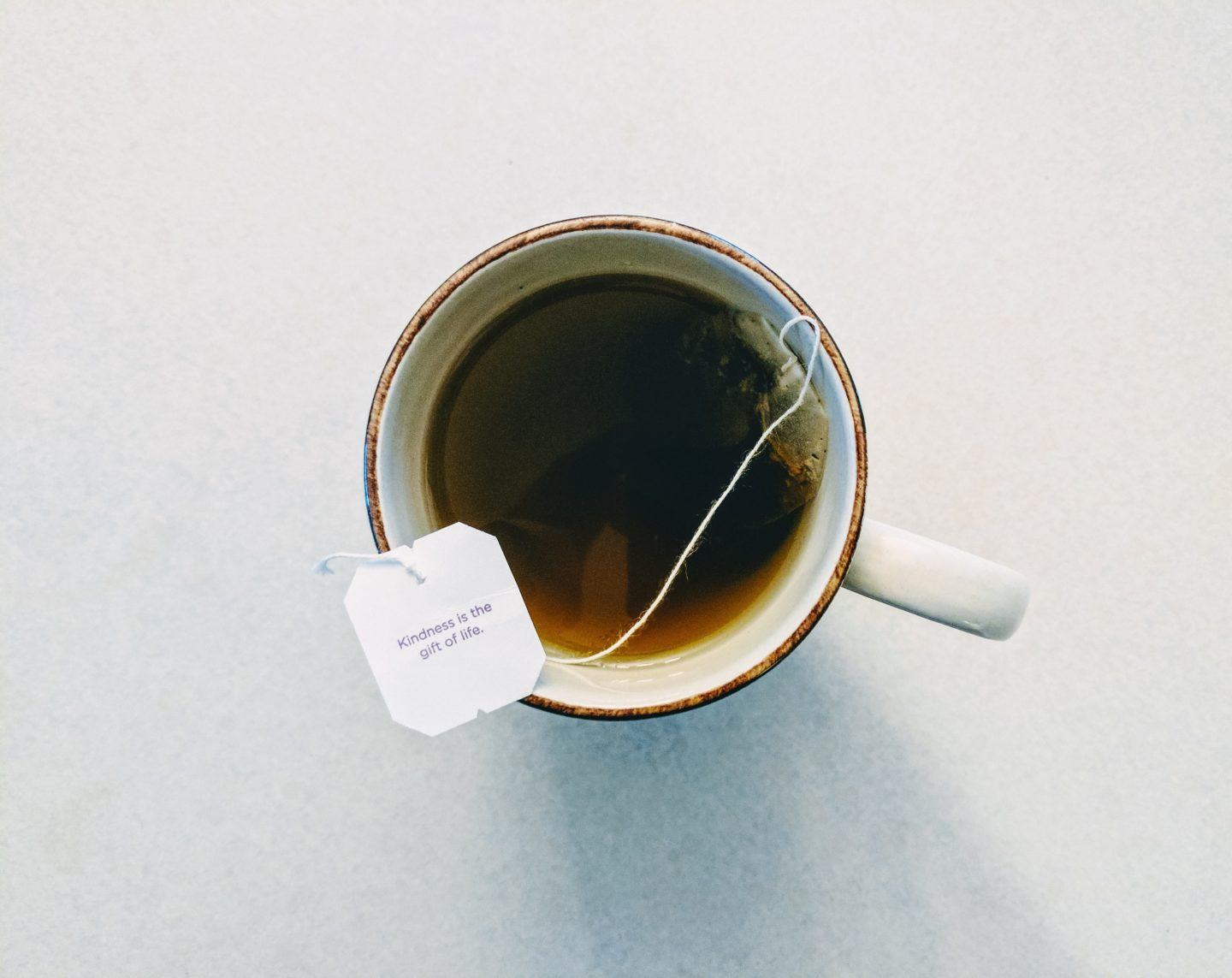 "Cup of tea with tag that says ""kindness is the gift of life."""