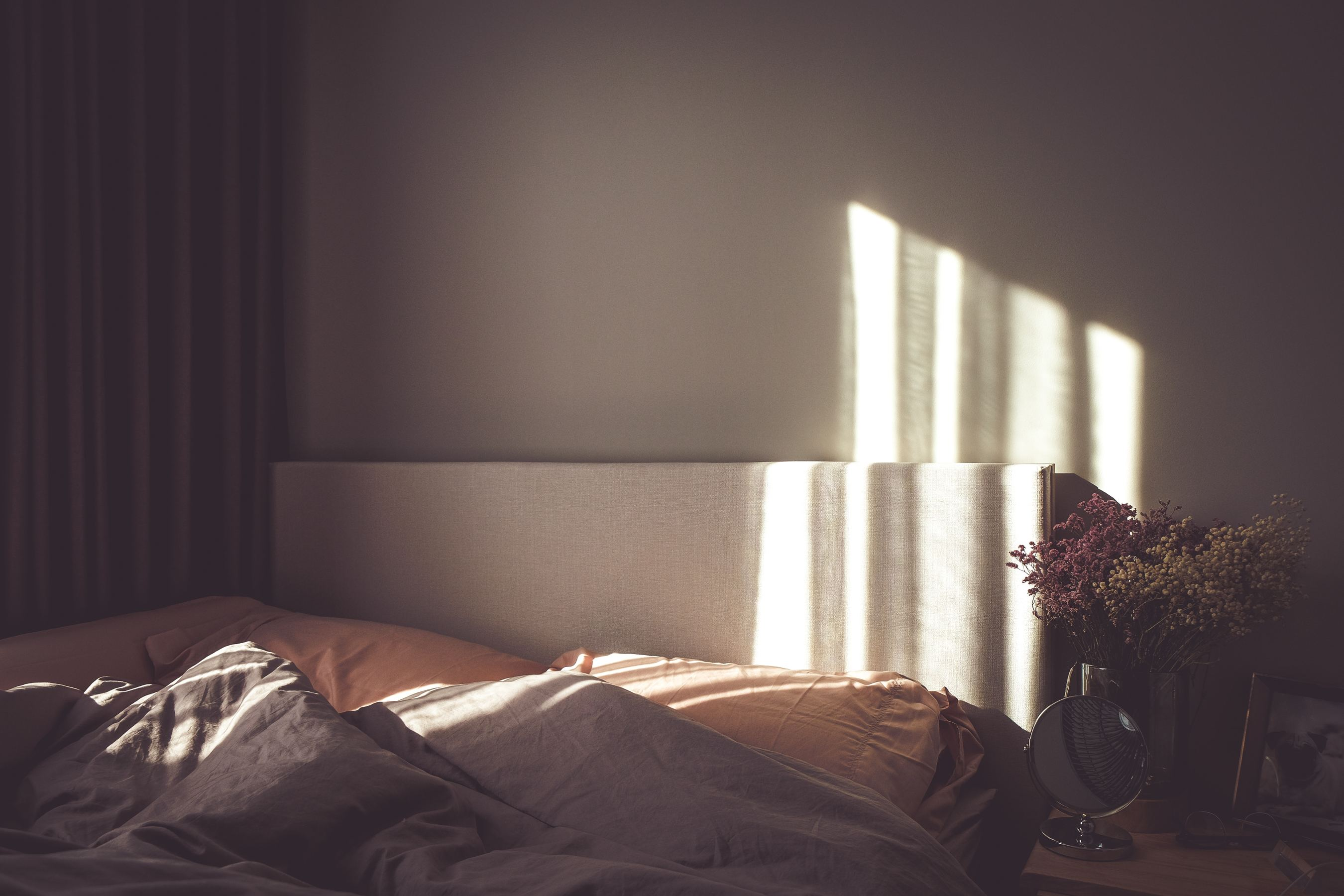 Cozy bed on a lay Sunday morning, the sun rise just starting to pour in