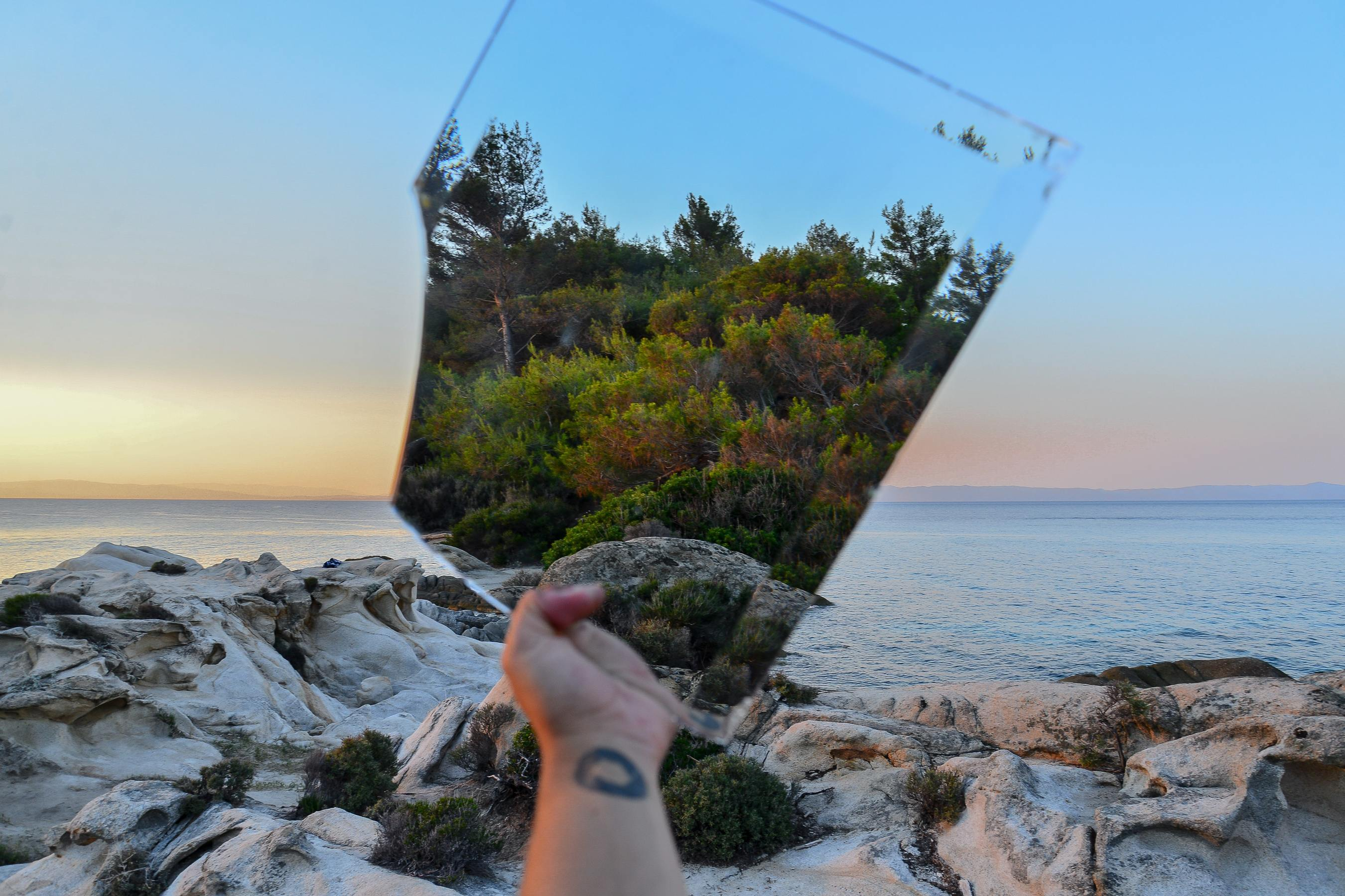 Person holding a mirror to reflect the environment behind them