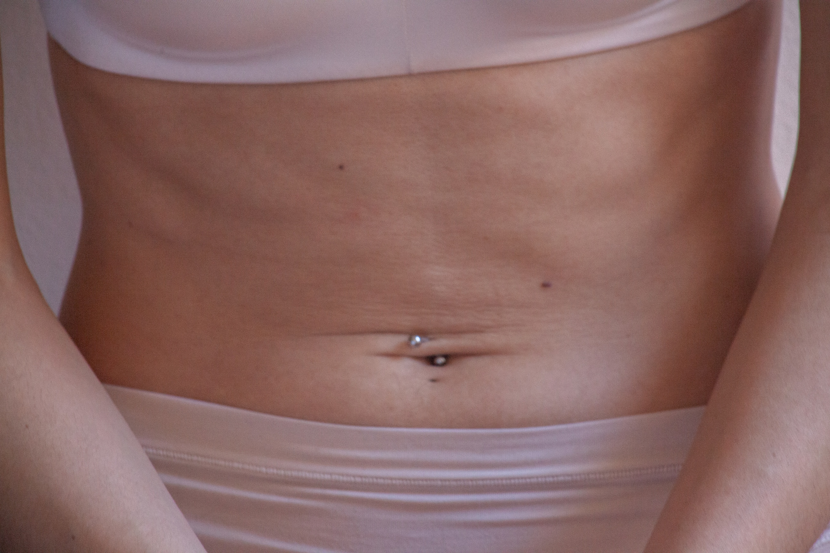 A bare tummy exposed, the person wearing flesh toned underwear