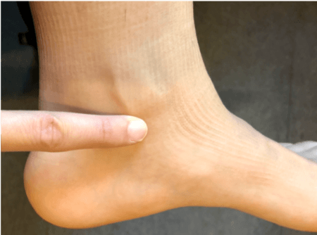one finger placed under ankle bone