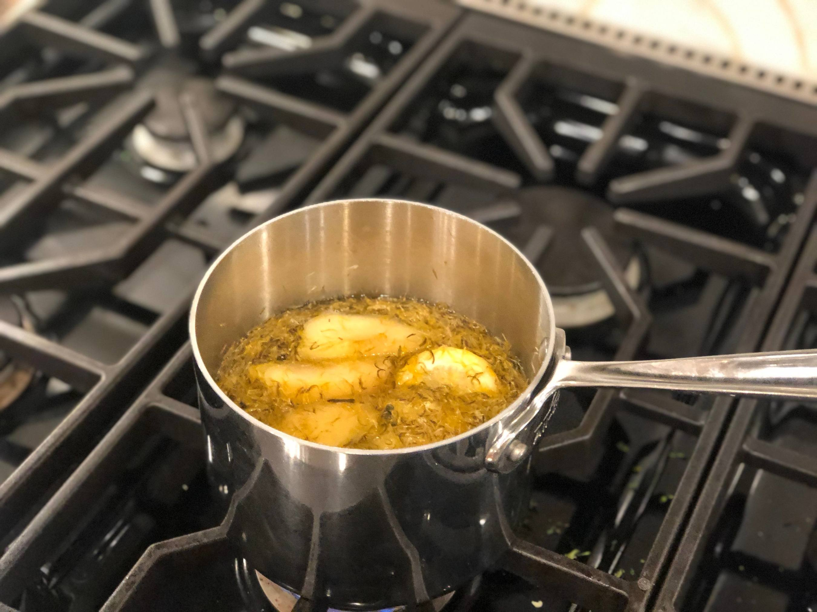 dandelions cooking on the stove in a metal pot
