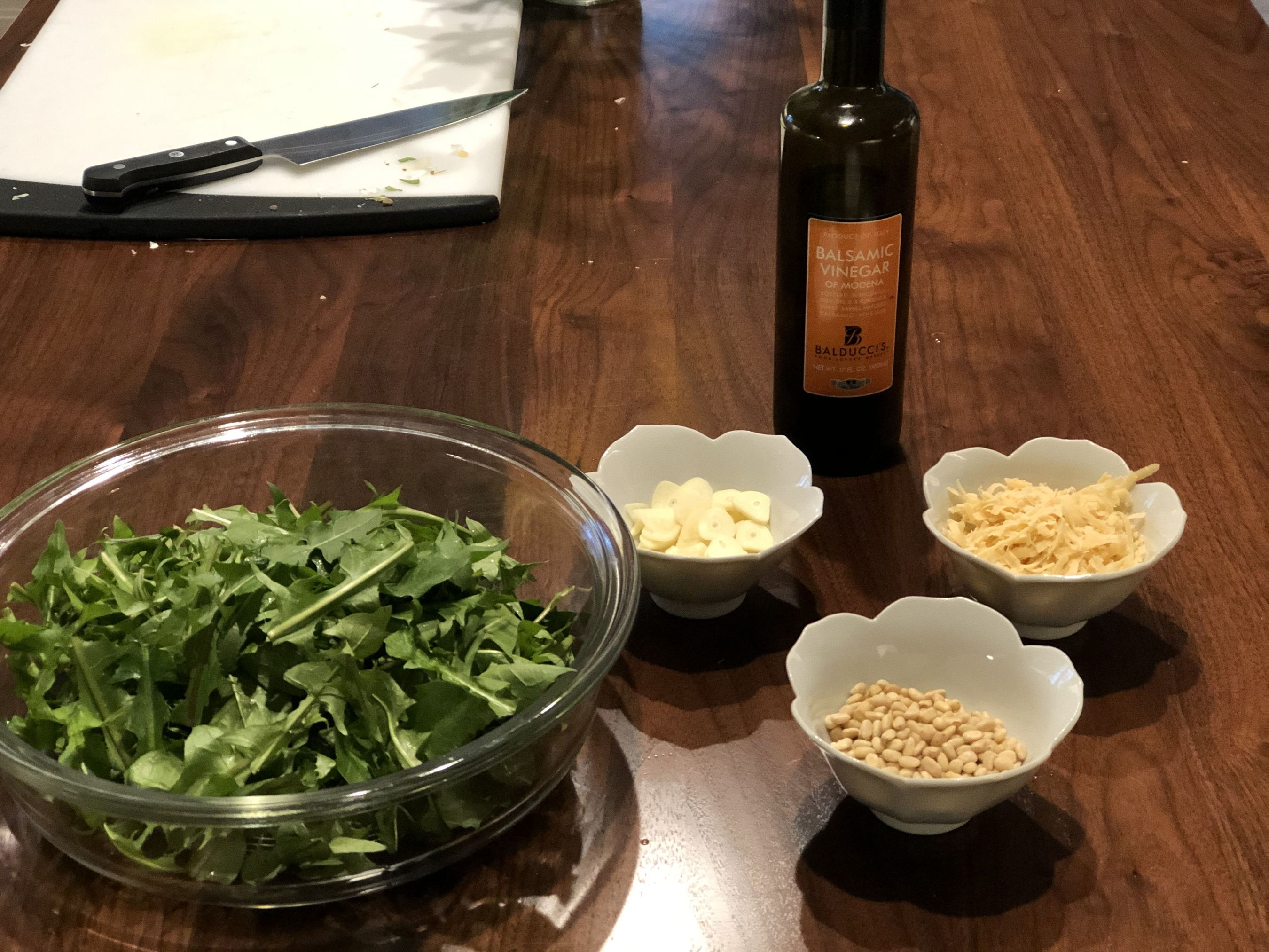 arugula, garlic, pine nuts, and olive oil on a table