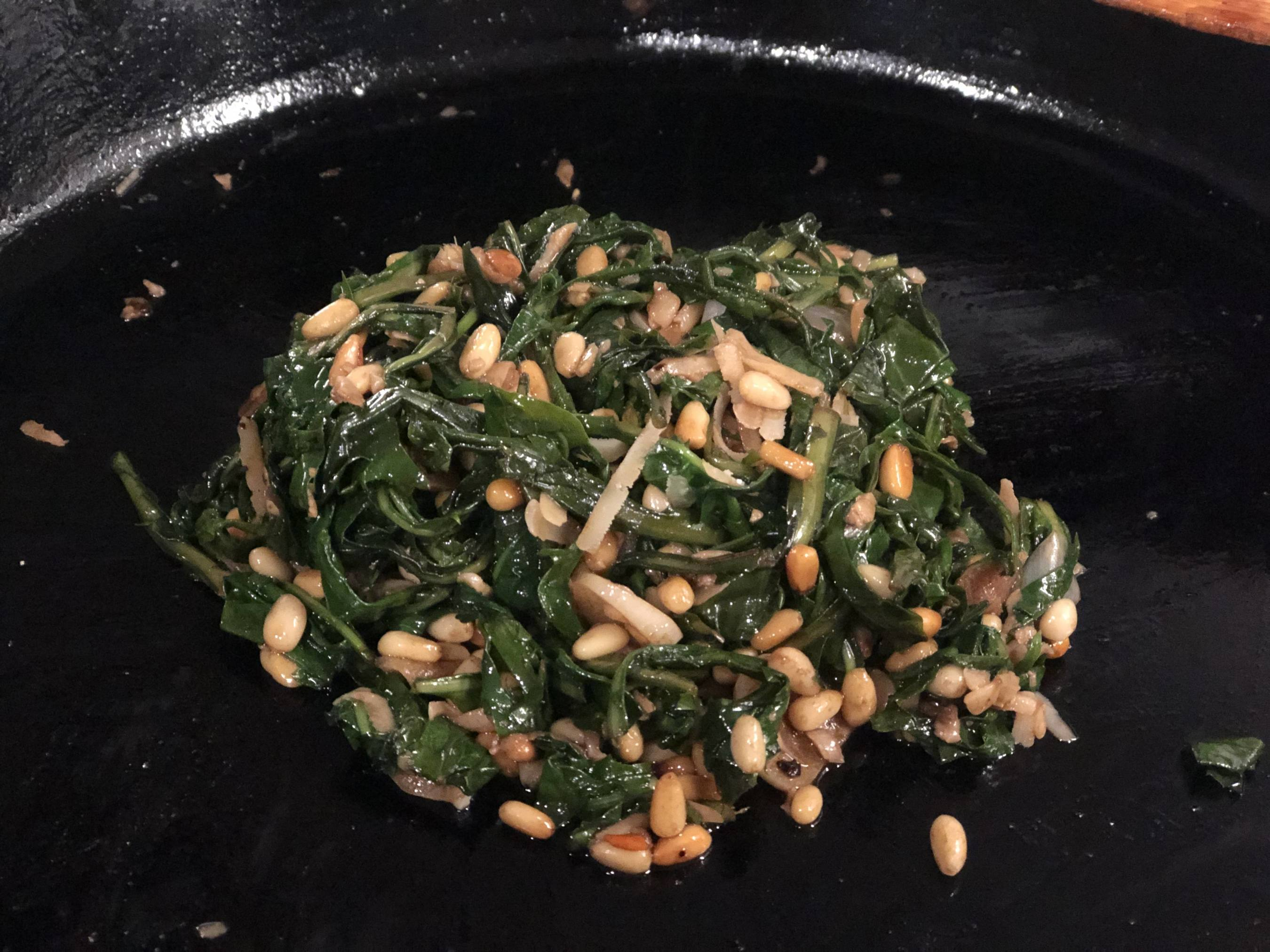 cooked dandelion greens with arugula, pine nuts, and parmesan cheese