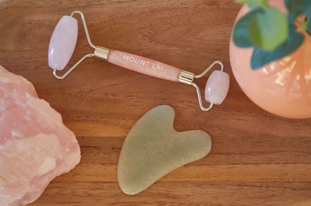 A rose quartz facial roller and a jade gua sha tool lay on a wooden table between a rose quarts crystal and a peach vase