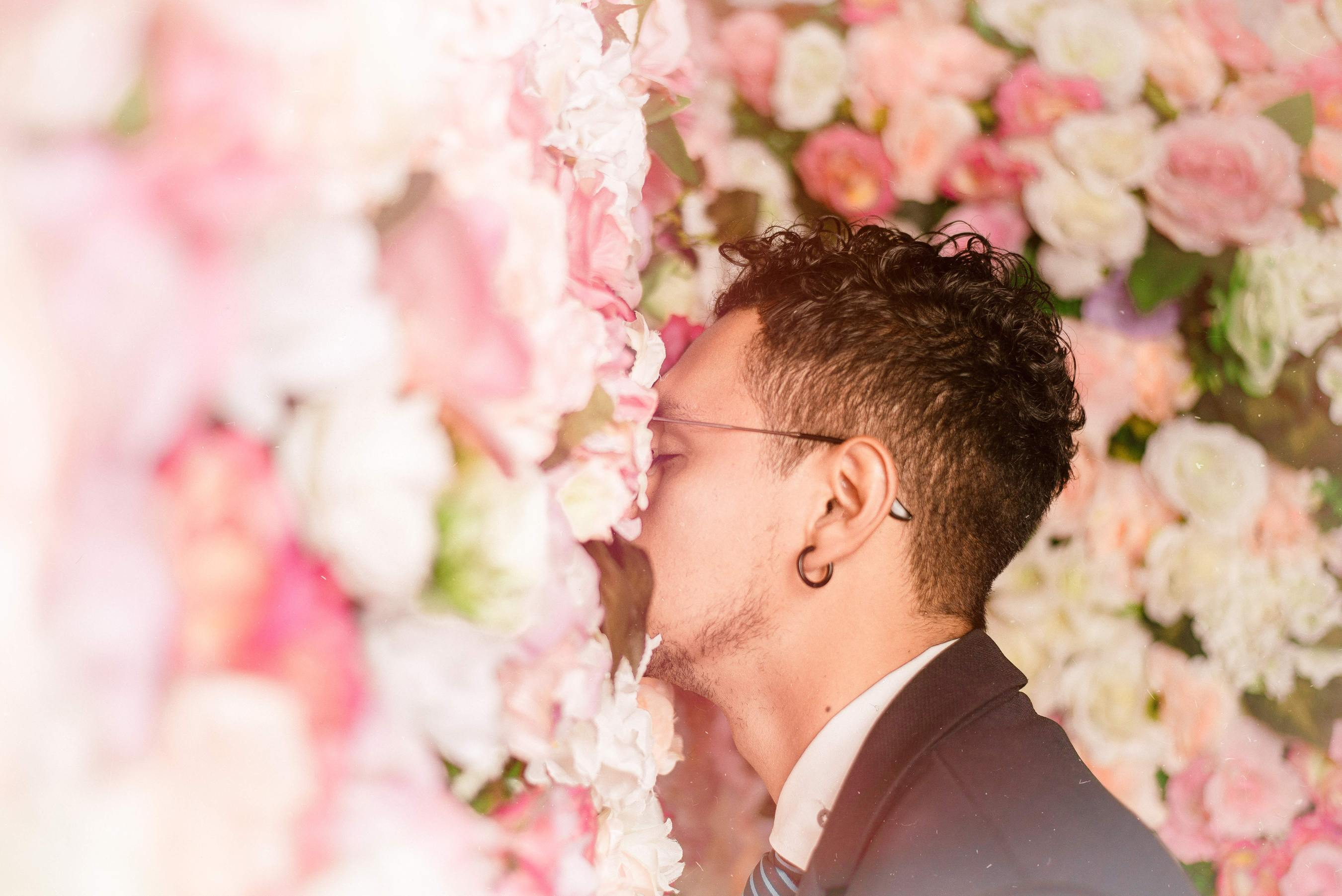 a man with his face in a wall of light pink roses