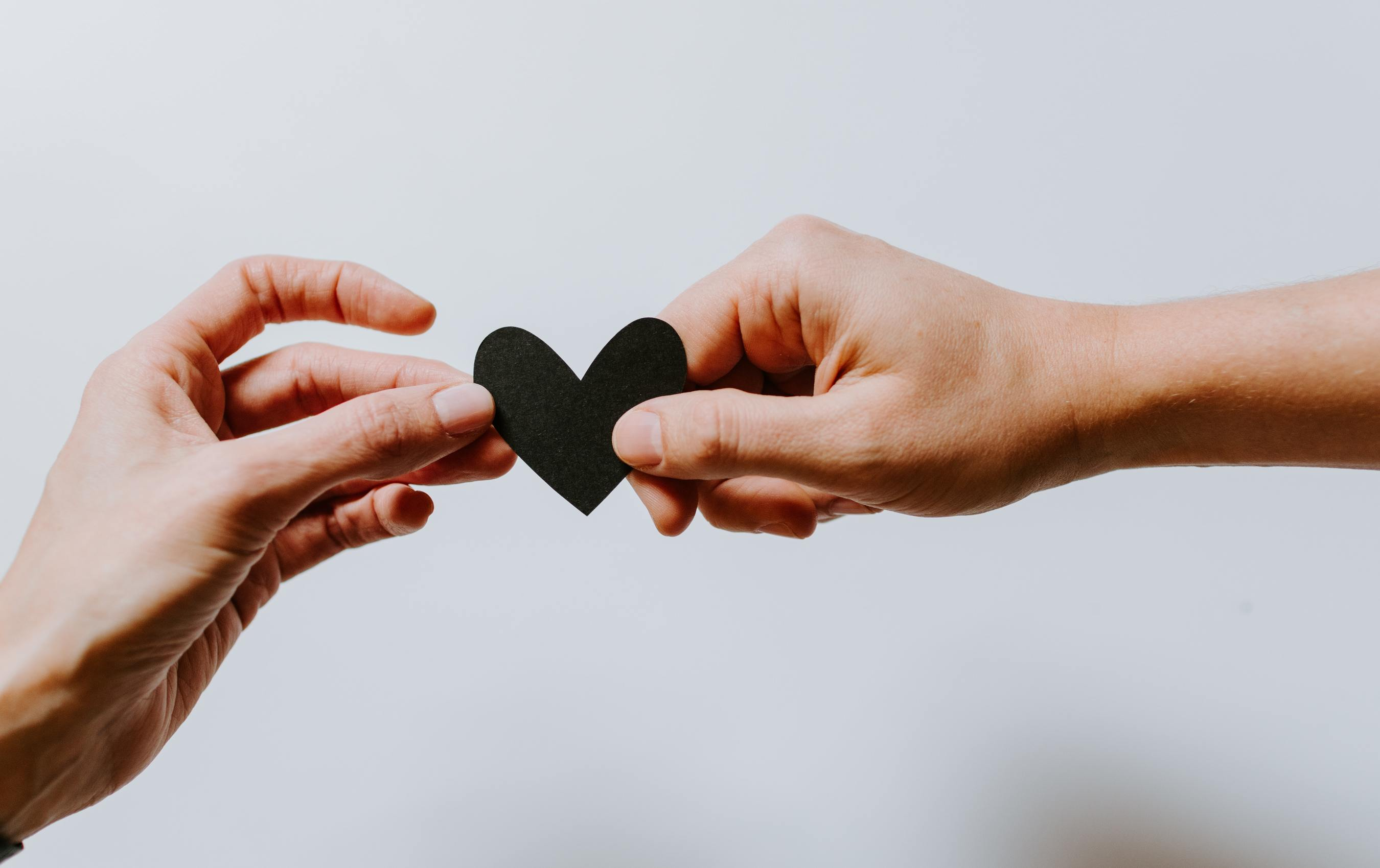 Two hands holding a heart paper together